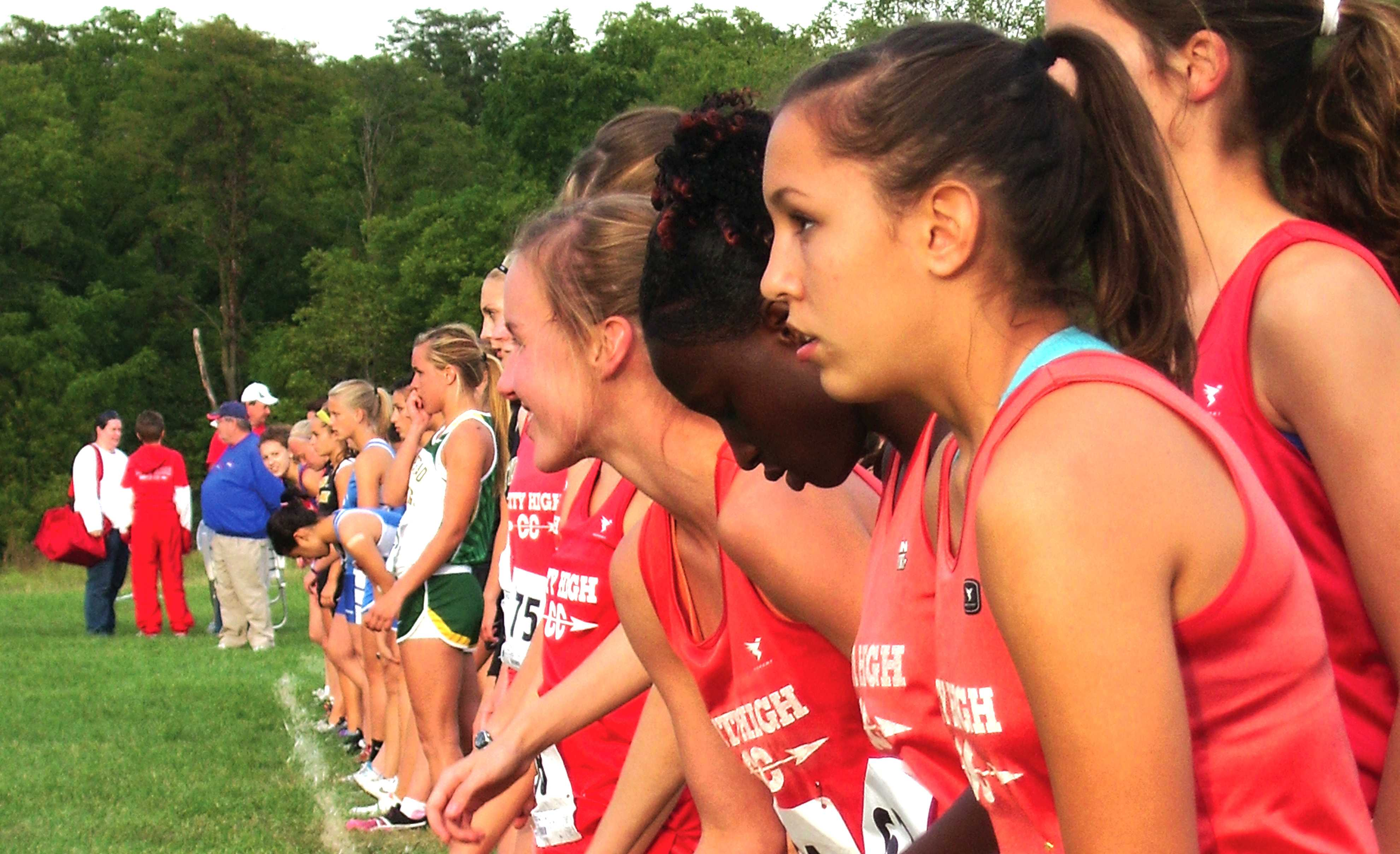 XC girls line up for the start of a race Photo by The Little Hawk