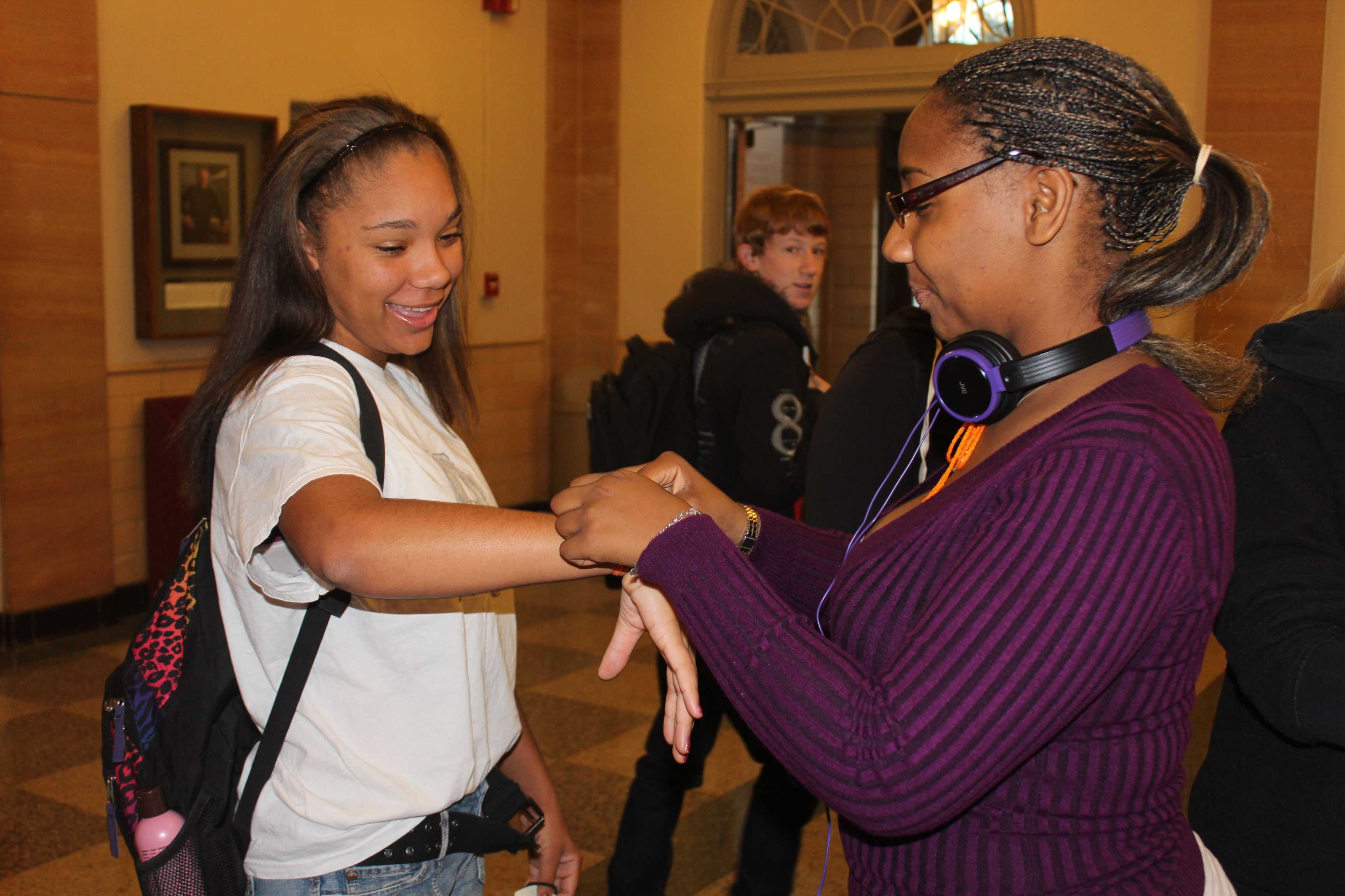 Students tie orange bracelets around their wrists in support of bullying prevention.  Photo by Jeff Morris